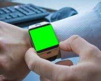 Geschäftsmann, der seine smartwatch APP mit Farbenreinheitsschlüssel-Grünschirm, Konzept der neuen Technologie verwendet Stockfotos