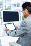 Geschäftsmann, der seine Tablette betrachtet Lizenzfreie Stockfotografie