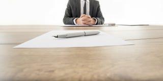Geschäftsmann, der an seinem hölzernen Schreibtisch mit Vertrag infr sitzt lizenzfreies stockfoto