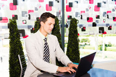 Geschäftsmann, der an seinem Laptop arbeitet Lizenzfreies Stockbild