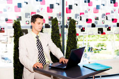 Geschäftsmann, der an seinem Laptop arbeitet Lizenzfreie Stockfotos