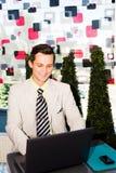 Geschäftsmann, der an seinem Laptop arbeitet Stockbild
