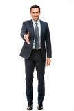 Geschäftsmann, der seinen Arm für das Rütteln von Händen anhebend lächelt Lizenzfreies Stockfoto