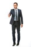 Geschäftsmann, der seinen Arm für das Rütteln von Händen anhebend lächelt Lizenzfreies Stockbild