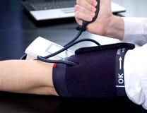 Geschäftsmann, der seinen Blutdruck misst Lizenzfreies Stockbild