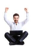 Geschäftsmann, der seinen Erfolg mit einem Computer feiert Stockbild