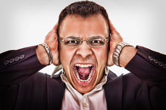 Geschäftsmann, der seinen Kopf und Schreie ergreift Stockfotografie