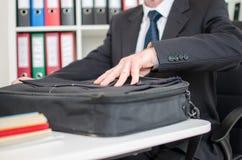 Geschäftsmann, der seinen Laptopkoffer öffnet Stockbild