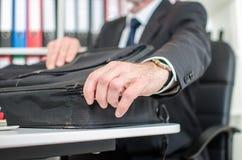 Geschäftsmann, der seinen Laptopkoffer öffnet Lizenzfreies Stockfoto