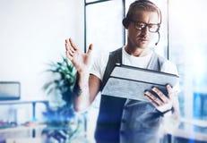 Geschäftsmann, der an seiner digitalen Tablette hält in den Händen arbeitet Eleganter Mann, der Audiokopfhörer trägt und Video he stockbild