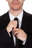 Geschäftsmann, der seins Gleichheit geraderichtet stockfoto