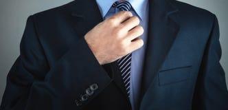Geschäftsmann, der seins Gleichheit regelt stockfotografie