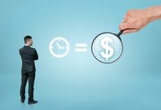 Geschäftsmann, der Seufzer u. x27 betrachtet; Zeit ist money& x27; mit großem man& x27; s-Handvergrößerungsdollarzeichen durch Ve Lizenzfreie Stockbilder
