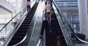 Geschäftsmann, der sich unten auf Rolltreppe in einem modernen Büro 4k verschiebt stock video footage