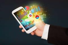 Geschäftsmann, der Smartphone mit Diagrammsymbolen hält Stockfotografie