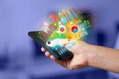 Geschäftsmann, der Smartphone mit Diagrammsymbolen hält Lizenzfreies Stockfoto