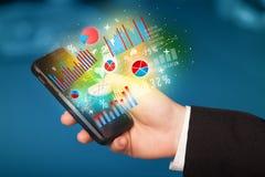 Geschäftsmann, der Smartphone mit Diagrammsymbolen hält Lizenzfreies Stockbild