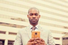 Geschäftsmann, der in Stadt mit Handy geht Stockbild