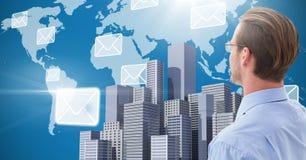 Geschäftsmann, der Stadt mit Weltkarte- und E-Mail-Ikonen gegenüberstellt stockfotografie