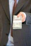 Geschäftsmann, der Stapel Dollar gibt. Nahaufnahme. Lizenzfreies Stockbild