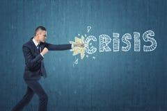Geschäftsmann, der stark das Wort ` Krise ` geschrieben auf dunkelblaue Wand locht Stockfotos