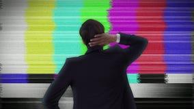 Geschäftsmann, der statisches Fernsehen betrachtet stock footage