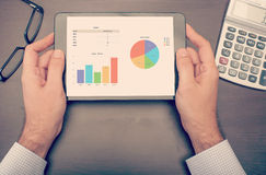 Geschäftsmann, der Statistiken über Tablettengerät überprüft lizenzfreie stockbilder