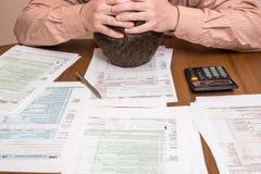 Geschäftsmann, der Steuer USA 1040 ergänzt Stockfotos