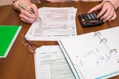 Geschäftsmann, der 1040 Steuerformular ergänzt Stockfotografie