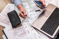 Geschäftsmann, der 1040 Steuerformular mit Hilfslaptop füllt Lizenzfreie Stockfotografie