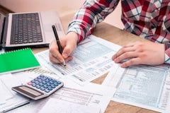 Geschäftsmann, der 1040 Steuerformular mit Hilfslaptop füllt Lizenzfreies Stockfoto