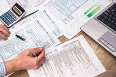 Geschäftsmann, der 1040 Steuerformular mit Hilfslaptop füllt Stockfotografie