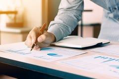 Geschäftsmann, der Stift auf Diagramm des zusammenfassenden Berichtes des Schreibarbeitsdiagramms zeigt Stockfoto