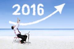 Geschäftsmann, der am Strand mit Nr. 2016 arbeitet Stockbilder