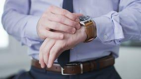 Geschäftsmann, der Stunde auf seiner Uhr überprüft stock video footage