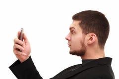 Geschäftsmann, der surprisedly Telefon betrachtet Stockbild