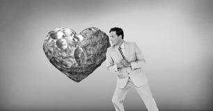 Geschäftsmann, der am surrealen Herzen sich lehnt stockfotos