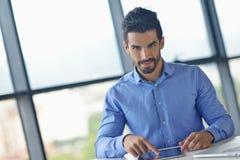 Geschäftsmann, der Tablette compuer im Büro verwendet Lizenzfreie Stockfotos
