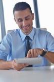 Geschäftsmann, der Tablette compuer im Büro verwendet Lizenzfreie Stockbilder