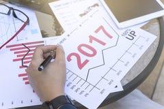 Geschäftsmann, der Tablette für die analytische Finanztendenzvoraussage des diagrammjahres 2017 plant Platz im Freien verwendet Stockfotos