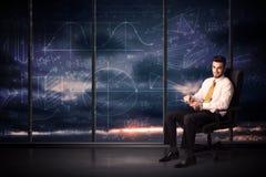Geschäftsmann, der Tablette im Büroraum mit Diagrammdiagrammen auf w hält Stockfotografie