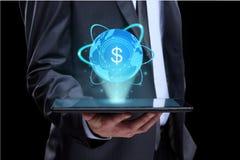 Geschäftsmann, der Tablette mit einem hervorstehenden Bildschirmikonenonlinehandeldollar hält Karte mit beschrifteten Kontinenten Stockfotos