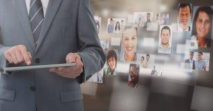 Geschäftsmann, der Tablette mit Leute ` s Profilbildern im Büro hält Stockbild