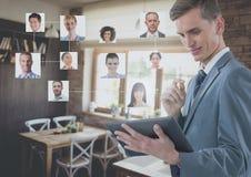 Geschäftsmann, der Tablette mit Leute ` s Profilbildern im Caférestaurant hält Stockfotos