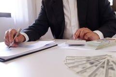 Geschäftsmann, der Taschenrechner mit Geld auf dem Schreibtisch verwendet lizenzfreies stockfoto