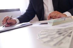 Geschäftsmann, der Taschenrechner mit Geld auf dem Schreibtisch verwendet stockbild