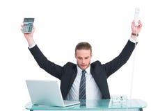 Geschäftsmann, der Taschenrechner und Telefon halten zujubelt Lizenzfreies Stockbild