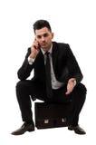 Geschäftsmann, der am Telefon beim Sitzen auf einem Aktenkoffer spricht Stockfotografie