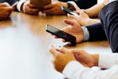 Geschäftsmann, der Telefon beim Warten den App oder auf die Website, um im Büro zu laden verwendet stockbilder