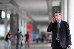 Geschäftsmann, der am Telefon in der Menge spricht Stockbild